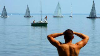 Tihany, 2018. augusztus 20. Sportoló fiatal vitorlázó társainak megérkezését és kikötését nézi a Balaton-partról nyári napsütésben. MTVA/Bizományosi: Jászai Csaba  *************************** Kedves Felhasználó! Ez a fotó nem a Duna Médiaszolgáltató Zrt./MTI által készített és kiadott fényképfelvétel, így harmadik személy által támasztott bárminemû – különösen szerzõi jogi, szomszédos jogi és személyiségi jogi – igényért a fotó készítõje közvetlenül maga áll helyt, az MTVA felelõssége e körben kizárt.