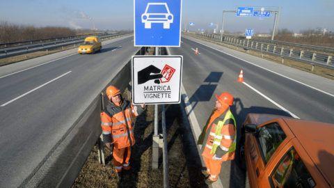 Dunakeszi, 2014. december 31.A Magyar Közút Nonprofit Zrt. munkatársai helyeznek ki egy a fizetős autópálya-szakaszt jelző táblát az M0-ás autóúton, az M3-as autópálya lehajtójának közelében 2014. december 31-én.MTI Fotó: Máthé Zoltán