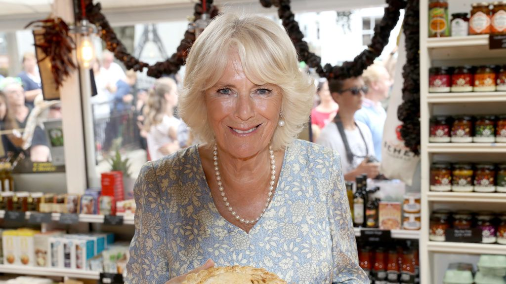 FOWEY, CORNWALL - JULY 16:  Camilla, Duchess Of Cornwall with a Cornish Pasty as she tours local businesses with Prince Charles, Prince Of Wales during the Fowey Festival Celebration on day one of their visit to Devon and Cornwall on July 16, 2018 in Fowey, United Kingdom.  (Photo by Chris Jackson/Getty Images)