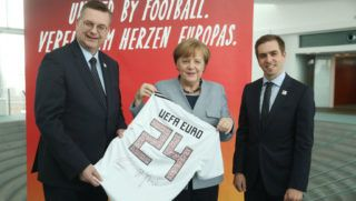 BERLIN, GERMANY - MARCH 27:  Reinhard Grindel (L), President of the German Football Federation (DFB), German Chancellor Angela Merkel and retired German football star Philipp Lahm hold up a t-shirt signed by Lahm and Grindel as a gift for the Chancellor ahead of the UEFA EURO 2024 on March 27, 2018 in Berlin, Germany.  (Photo by Sean Gallup/Bongarts/Getty Images)