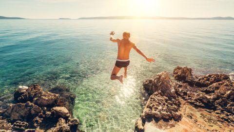 Man jumps in blue sea lagoon water