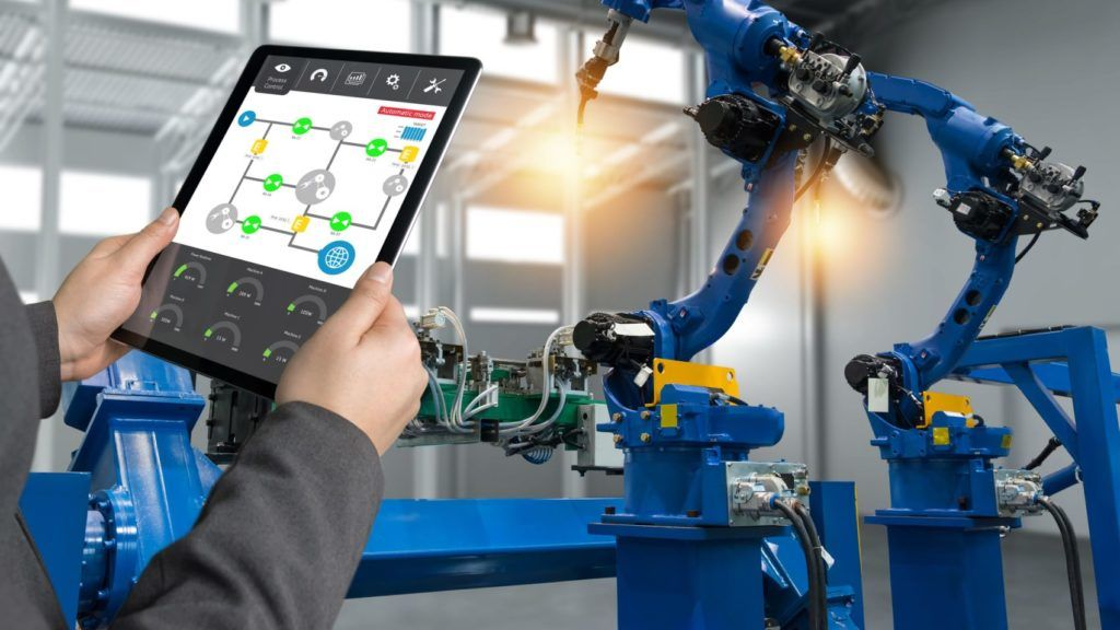 Engineer hand using tablet, heavy automation robot arm machine in smart factory industrial with tablet real time process control monitoring system application. Industry 4th iot concept.