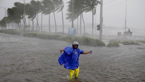 Manila, 2018. szeptember 15. Forgalomirányító a Mangkhut tájfun által okozott viharban, Manilában 2018. szeptember 15-én. A természeti csapás legkevesebb három halálos áldozatot követelt, több mint ötvenezer embernek kellett elhagynia othonát. (MTI/AP/Bullit Marquez)