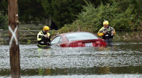New Bern, 2018. szeptember 15. Mentõalakulat tagjai egy elmerült autónál a Florence hurrikán által okozott heves esõzésekben elöntött utcán az észak-karolinai New Bernben 2018. szeptember 15-én. Az Atlanti-óceán felõl érkezõ hurrikán  trópusi viharrá szelídült, de változatlanul veszélyes, több halálos áldozatot követelt. (MTI/AP/Chris Seward)