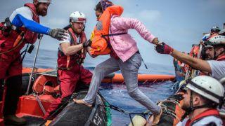 Földközi-tenger, 2018. április 21.Afrikai migránsnak segítenek gumicsónakba szállni az illegális bevándorlók tengeri mentését végző SOS Mediterranee civil szervezet Aquarius nevű hajója legénységének tagjai a Földközi-tengeren 2018. április 21-én. Az Aquarius mintegy 250 csónakban utazó illegális bevándorlót vett a fedélzetére a líbiai partoktól mintegy 50 kilométerre. (MTI/EPA/Christophe Petit Tesson)