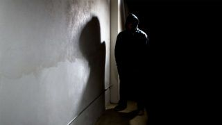 Photo of a hooded criminal stalking in the shadows of a dark street alley.  The hooded man is a silhouette and hiding in the dark.  The man is a criminal waiting to ambush victims.  The concrete walls provide copyspace.The photo depicts crime.