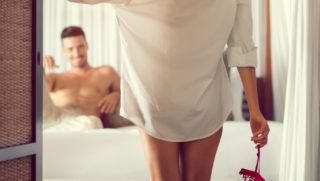 Attractive seductive woman at the bedroom door while her boyfriend lying in bed