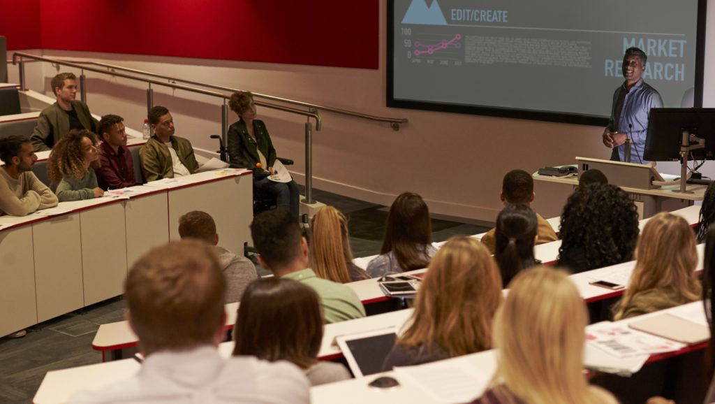 Young adult students at a university lecture, back view
