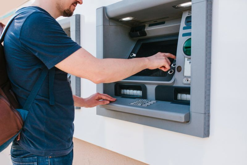 The tourist withdraws money from the ATM for further travel. Finance, credit card, withdrawal of money. Journey. Vacation.
