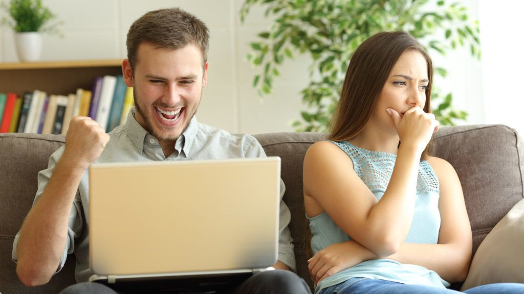 Luddite husband betting on line with a laptop ignoring his sad wife sitting on a couch at home