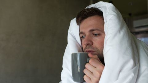 Caucasian male with lack of sleep because he has flu stting in bed and ask for water or medicine. Concept ob being ill alone. Nobody can help him