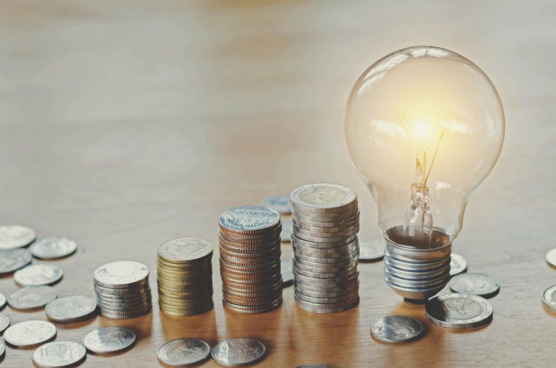 stack money coins with growing light bulb concept