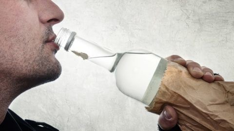Man is drinking vodka from the bottle, alcoholism concept.