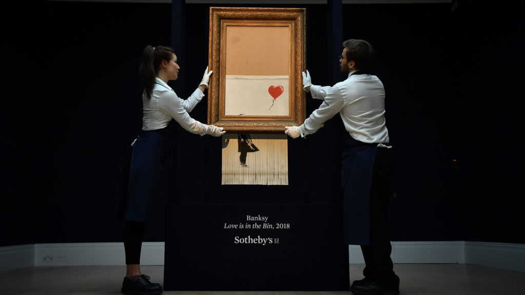 """Sotheby's employees pose with the newly completed work by artist Banksy entitled """"Love is in the Bin"""", a work that was created when the painting """"Girl with Balloon"""" was passed through a shredder in a surprise intervention by the artist, at Sotheby's auction house in London on October 12, 2018, following the work's sale. - The buyer of a work by street artist Banksy that was partially destroyed moments after it sold has gone through with the purchase, Sotheby's auction house said on October 11, 2018. The painting """"Girl with Balloon"""" was passed through a shredder hidden in the frame just after it went under the hammer last week for Ł1,042,000 ($1.4 million, 1.2 million euros). The modified version has now been certified by Banksy's authentication body Pest Control as a new piece of work in its own right, entitled """"Love is in the Bin"""". (Photo by Ben STANSALL / AFP) / RESTRICTED TO EDITORIAL USE - MANDATORY MENTION OF THE ARTIST UPON PUBLICATION - TO ILLUSTRATE THE EVENT AS SPECIFIED IN THE CAPTION"""