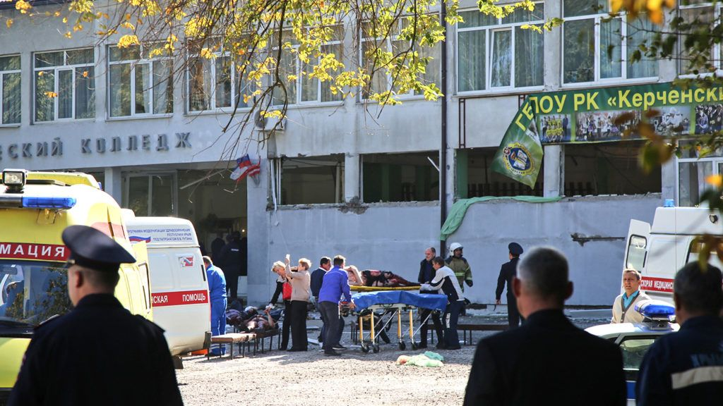 """Rescuers carry an injured victim of a blast at at a college in the city of Kerch on October 17, 2018. - Thirteen people were killed and 50 more wounded, most of them teenagers, after a blast tore into a college canteen in Russian-annexed Crimea in what Moscow called a """"terrorist"""" attack. (Photo by - / KERCH.FM / AFP)"""