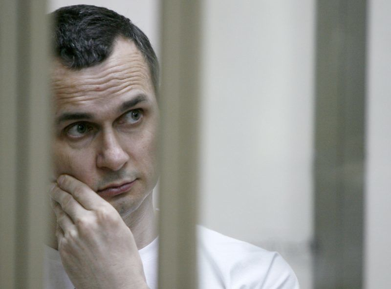 Ukrainian film director Oleg Sentsov stands inside a defendants' cage during a hearing at a military court in the city of Rostov-on-Don on July 21, 2015. A Ukrainian film director went on trial on terror charges in southern Russia on July 21, after Moscow held him for more than a year in a case decried by Kiev, rights groups and prominent film directors across the globe. AFP PHOTO / SERGEI VENYAVSKY (Photo by SERGEI VENYAVSKY / AFP)