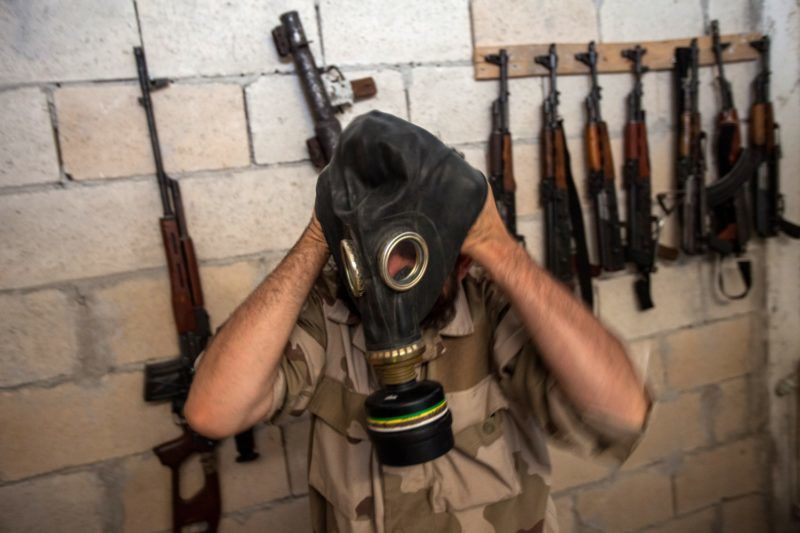 A Syrian rebel tries on a gas mask seized from a Syrian army factory in the northwestern province of Idlib on July 18, 2013. Western countries say they have handed over evidence to the UN that Bashar al-Assad's forces have used chemical arms in the two-year conflict. More than 100,000 people have died in the conflict, which morphed from a popular movement for change into an insurgency after the regime unleashed a brutal crackdown on dissent. AFP PHOTO/DANIEL LEAL-OLIVAS (Photo by Daniel LEAL-OLIVAS / DANIEL LEAL-OLIVAS / AFP)