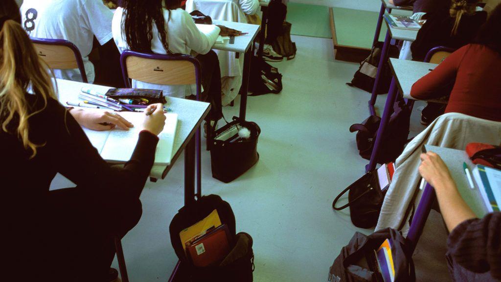France, Paris region, Maisons Alfort, Eugene Delacroix secondary school, pupils working in classroom, schoolbags on floor.