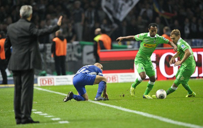 Gladbach's head coach Lucien Favre (L) gives directions to his players Tony Jantschke (R-L) and Raffael next to Berlin's Aenis Ben-Hatira during the Bundesliga soccer match between Hertha BSC Berlin and Borussia Moenchengladbachat Olympiastadion in Berlin, Germany, 19 October 2013. Photo: Ole Spata/dpa