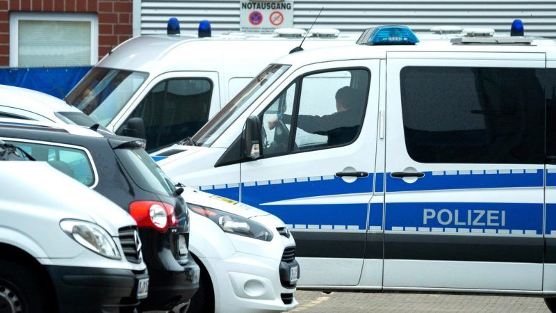 30 October 2018, Lower Saxony, Oldenburg: A police vehicle protects the prisoner transporter with the defendant Niels Högel at a rear entrance of the Weser-Ems-Halle before the trial begins. The trial of the regional court takes place in the Weser-Ems-Hallen because of the numerous parties involved in the trial. The public prosecutor's office has accused the former nurse of murdering 100 patients at clinics in Delmenhorst and Oldenburg. . Photo: Hauke-Christian Dittrich/dpa