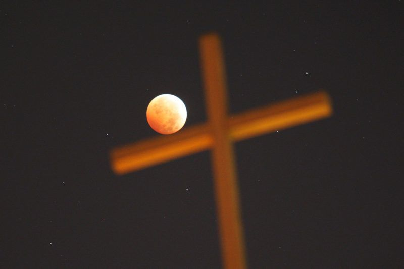 """LOS ANGELES, CA - OCTOBER 8: A religious cross is seen as the moon is illuminated by sunlight reflected off the Earth during a total lunar eclipse, one of four so-called """"blood moons"""", on October 8, 2014 in Los Angeles, California. The first in the current tetrad of blood moons fell on Passover and the current eclipse occurs on the Jewish holiday of Sukkot, the fifth day after Yom Kippur, leading some religious people to believe that it is a prophetic sign of the end times of civilization. This blood moon appears 5.3% larger than the last one on April 15 because it occurs right after the perigee, the closest point in its orbit to the Earth.   David McNew/Getty Images/AFP"""