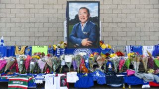 A portrait of Leicester City Football Club's Thai chairman Vichai Srivaddhanaprabha, who died in a helicopter crash at the club's stadium, is seen amid flowers and tributes outside the King Power Stadium in Leicester, eastern England, on October 29, 2018. - Leicester City's chairman Vichai Srivaddhanaprabha was among five people killed when his helicopter crashed and burst into flames in the Premier League side's stadium car park moments after taking off from the pitch, the club said on October 28. A stream of fans already fearing the worst had laid out flowers, football scarves and Buddhist prayers outside the club's King Power stadium after Saturday's accident in tribute to the Thai billionaire boss -- the man they credit for an against-all-odds Premier League victory in 2016 (Photo by Paul ELLIS / AFP)