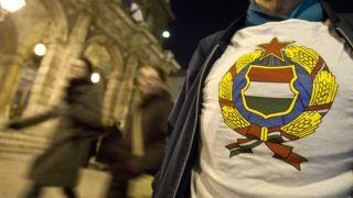 Budapest, 2011. március 5.A rendszerváltás előtti magyar címer egy munkáspárti aktivista pólóján, miközben érkeznek a nézők az árvíz- és belvízkárosultak megsegítésére rendezett jótékonysági gálaestre az Operaházba. A Szegények hangversenye - járdabál elnevezésű megmozdulást az általános szegénység elleni tiltakozásként értelmezik a szervezők.MTI Fotó: Szigetváry Zsolt