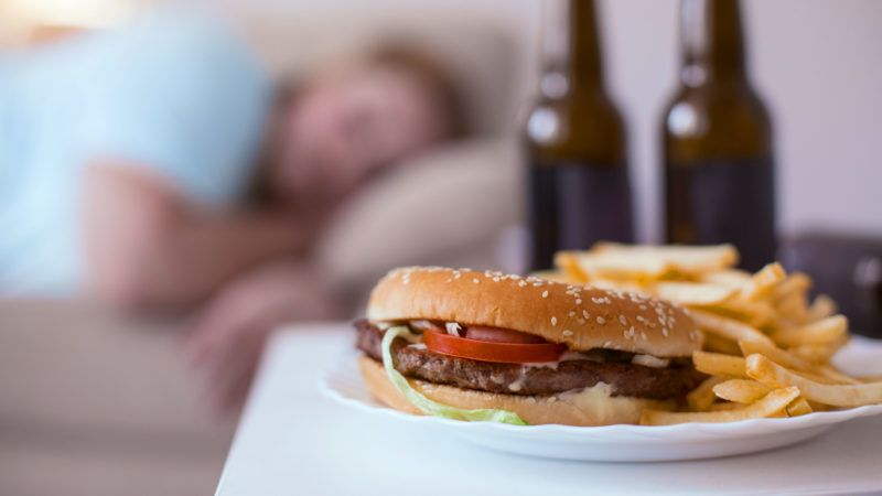 Junk food. Greasy nasty hamburger with fries lying on a plate