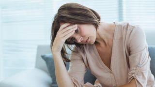 Sad young woman sitting on sofa at home