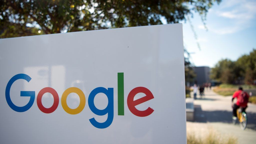"""(FILES) In this file photo taken on November 4, 2016 a man rides a bike pass a Google sign and logo at the Googleplex in Menlo Park, California.  Google on October 8, 2018 announced it is shutting down the consumer version of its online social network after fixing a bug exposing private data in as many as 500,000 accounts.The US internet giant said it will """"sunset"""" Google+ social network for consumers, which failed to gain meaningful traction as a challenge to Facebook.  / AFP PHOTO / JOSH EDELSON"""