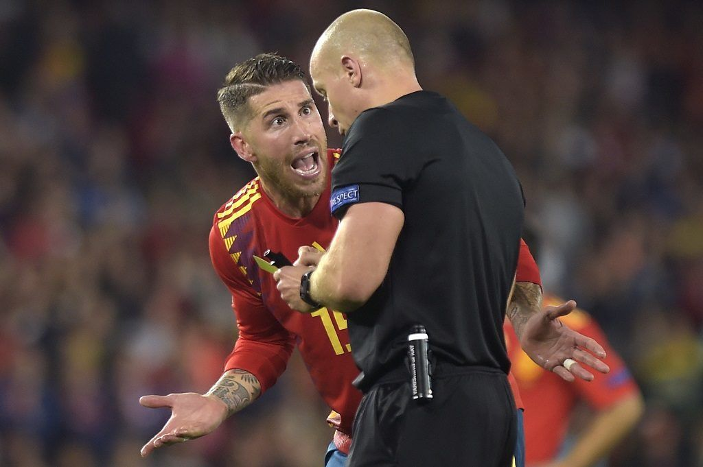 with Spain's defender Sergio Ramos (L) argues with Polish referee Szymon Marciniak during the UEFA Nations League football match between Spain and England on October 15, 2018 at the Benito Villamarin stadium in Sevilla. (Photo by JORGE GUERRERO / AFP)