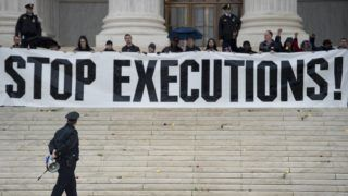 A police officer warns activists to leave during an anti death penalty protest in front of the US Supreme Court January 17, 2017 in Washington, DC. (Photo by Brendan Smialowski / AFP)