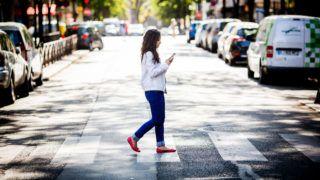 Woman using cell phone while crossing in a crosswalk.  Paris, France   GARO/PHANIE