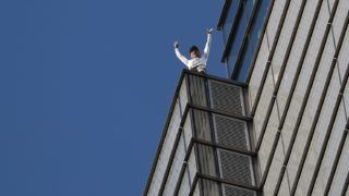 """French urban climber Alain Robert, also known as """"Spider-Man"""", reacts as he reaches the top of Heron Tower, 110 Bishopsgate, in central London on October 25, 2018, the tallest tower in the city of London. (Photo by Daniel LEAL-OLIVAS / AFP)"""