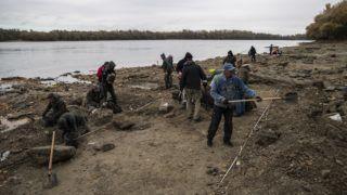 Érd, 2018. október 24. Régészeti feltárás az érdi Duna-parton 2018. október 24-én. Ezen a helyen nagy mennyiségû pénzérmét, fegyvereket, használati tárgyak maradványait tárták fel a szentendrei Ferenczy Múzeumi Centrum (FMC) régészei. A leletegyüttes egy 18. század közepén elsüllyedt hajóról kerülhetett a folyóba. MTI/Mónus Márton