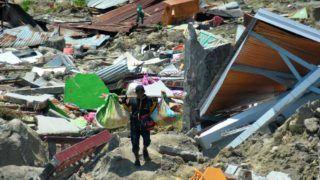 Palu, 2018. október 1. A romok közül kimentett holmikat viszi egy férfi az indonéziai Celebeszen (Sulawesi) fekvõ Paluban 2018. október 1-jén. A három nappal korábban történt 7,7-es erõsségû földrengésnek és az azt követõ szökõárnak a legfrissebb összesítések szerint legkevesebb 830 halottja és több száz sérültje van. (MTI/AP/Rifki)