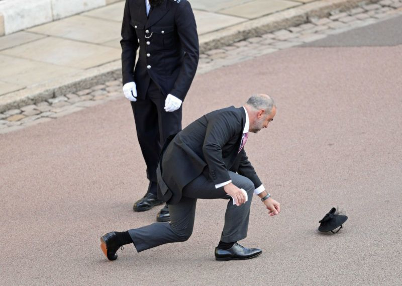 WINDSOR, ENGLAND - OCTOBER 12: A guest has his hat blown off in the wind ahead of the wedding of Princess Eugenie of York and Mr. Jack Brooksbank at St. George's Chapel on October 12, 2018 in Windsor, England. (Photo by Aaron Chown - WPA Pool/Getty Images)