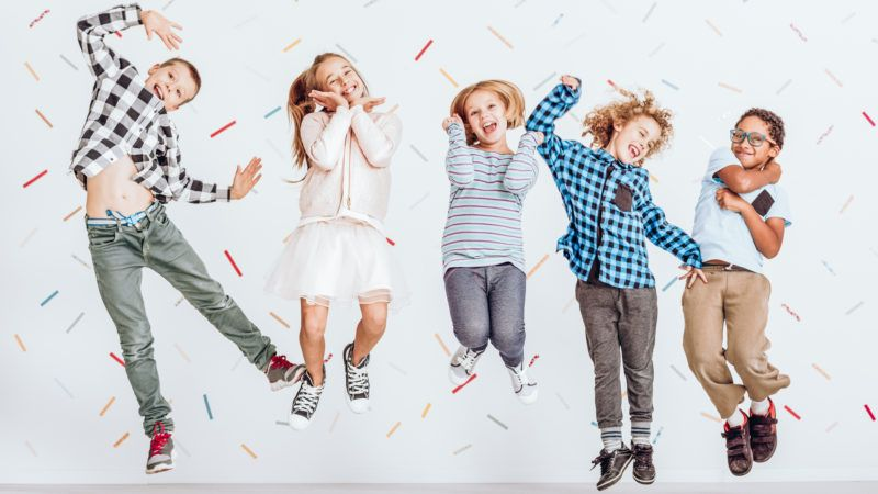 Happy group of kids jumping in a room with decorative tape on the wall