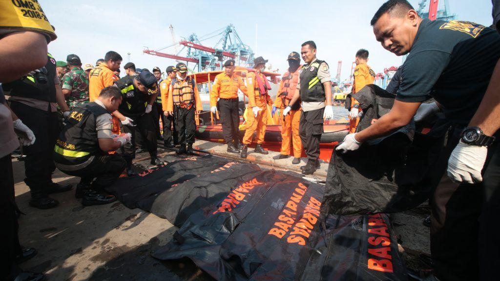 Tanjung Karawang, 2018. október 29. Az indonéziai nemzeti katasztrófavédelmi ügynökség, a BASARNAS tagjai letakarják az indonéz Lion Air légitársaság utasszállító repülõgépének tengerbõl kihalászott áldozatait Tanjung Karawang kikötõjében 2018. október 29-én. A belföldi viszonylatban közlekedõ gép Jakartából a Szumátra melletti Bangka szigetre tartott. A légitársaság szóvivõje elmondta: mindössze 13 perccel a felszállás után elvesztették a kapcsolatot a Boeing 737-800 típusú géppel. A tengerbe zuhant repülõgép fedélzetén 178 felnõtt utas, egy gyerek és két csecsemõ utazott, a személyzet héttagú volt. MTI/EPA/Bagus Indahono