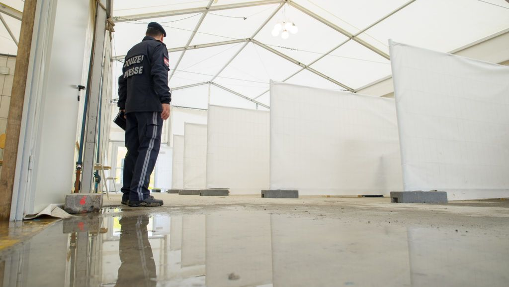 An Austrian police officer works at an empty refugee centre in Spielfeld at the Austrian-Slovenian border as Austria imposes a new daily migrant limit on February 19, 2016.   / AFP PHOTO / Rene Gomolj