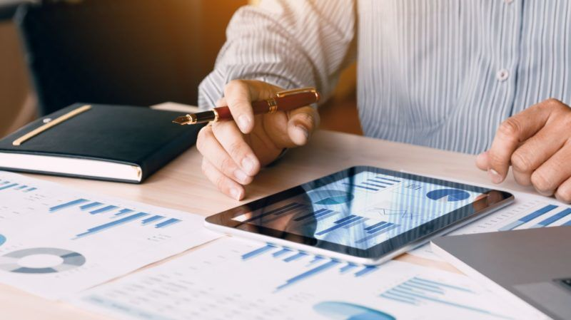 Businessman looking graph and summary report on digital tablet screen with analysis data result.