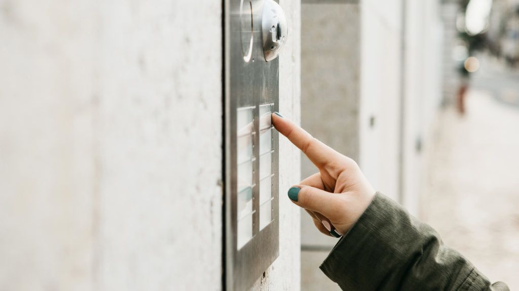 Close up the female hand presses the doorphone button. The girl is calling the intercom.