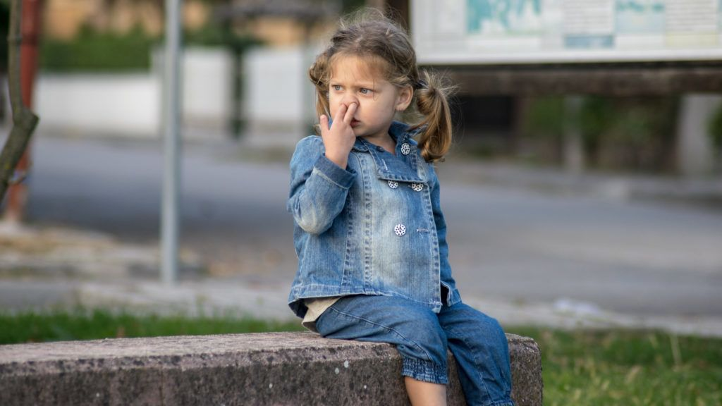 Picture of a funny little girl, with her finger in her nose