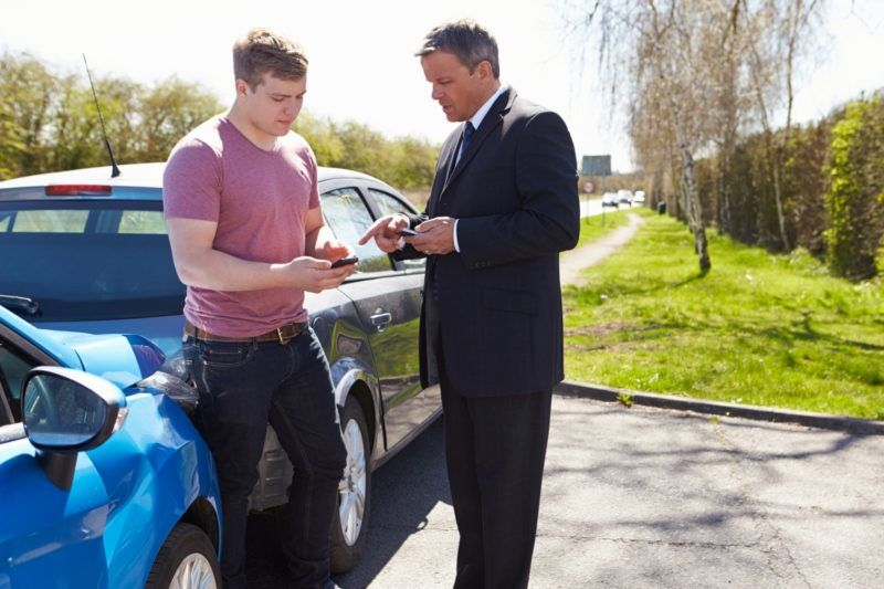 Two Drivers Exchange Insurance Details After Accident Using Mobile Phones