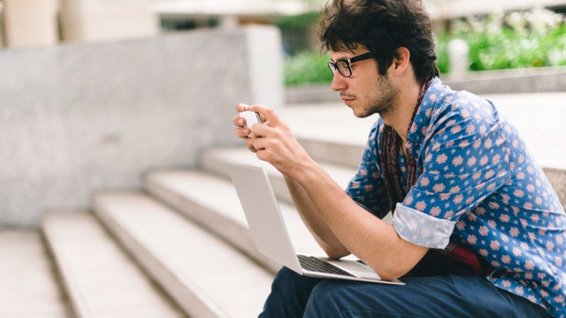 Caucasian student sitting on steps and using smartphone