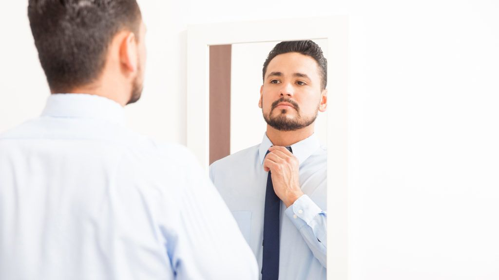 Portrait of an attractive young Hispanic man tying a knot on a necktie and looking at himself in a mirror