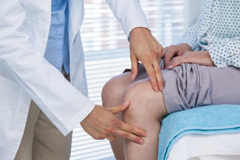 Mid section of doctor examining patient knee in clinic