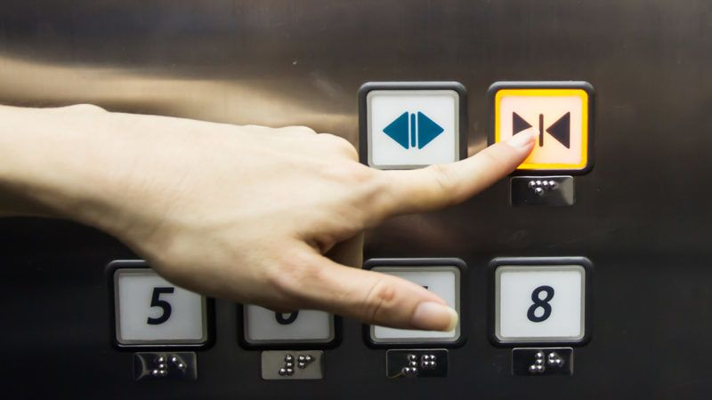 Elevator button is pushed by a female finger