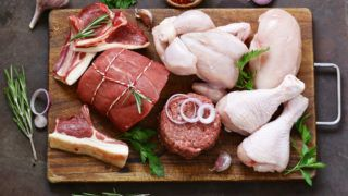 raw meat assortment - beef, lamb, chicken on a wooden board