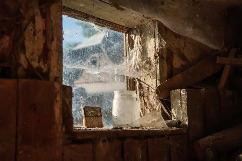 Interior view of a barn, window covered in dusty cobwebs. Selective focus